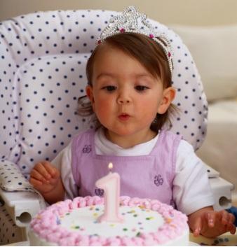 Малыш задувает свечу на свой первый день рождения